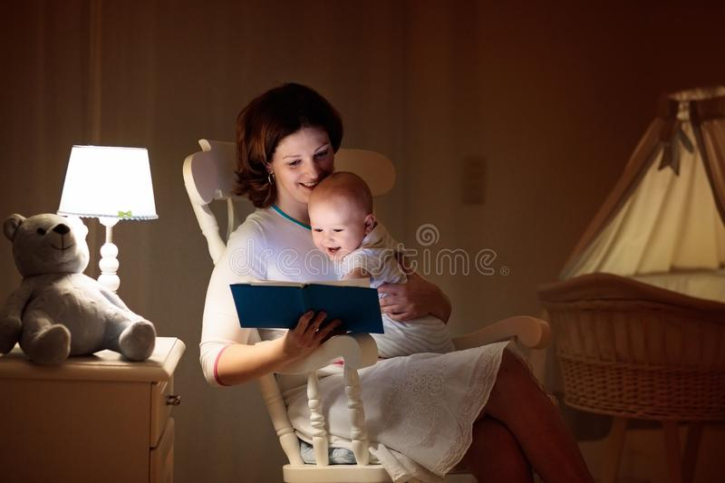 Mother reading a book to little baby stock photography