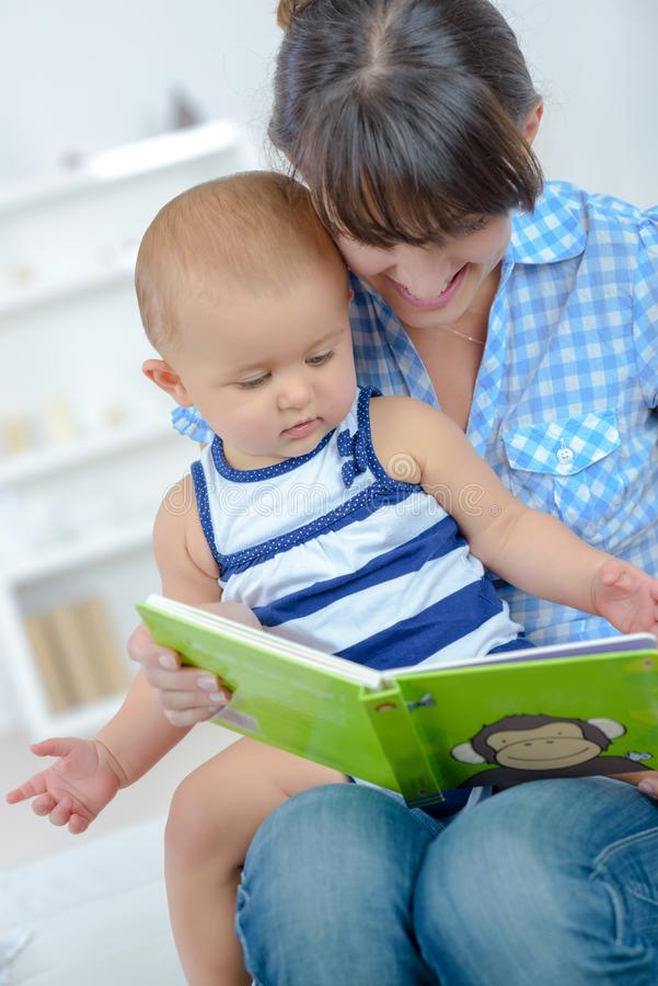 Mother and baby reading book together royalty free stock images