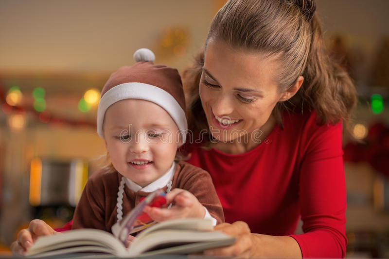 Mother and baby reading christmas book stock photo