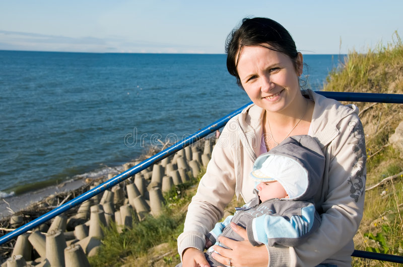 Mother with baby at sea shore. Mother is sitting on staircase and embracing her baby in arms at sea shore stock image