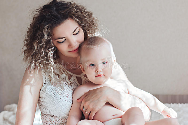 Mother and baby sitting on bed stock images