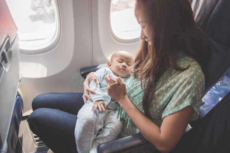 Mother and baby sitting together in airplane stock images