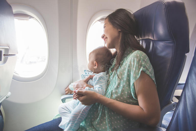 Mother and baby sitting together in airplane stock photos