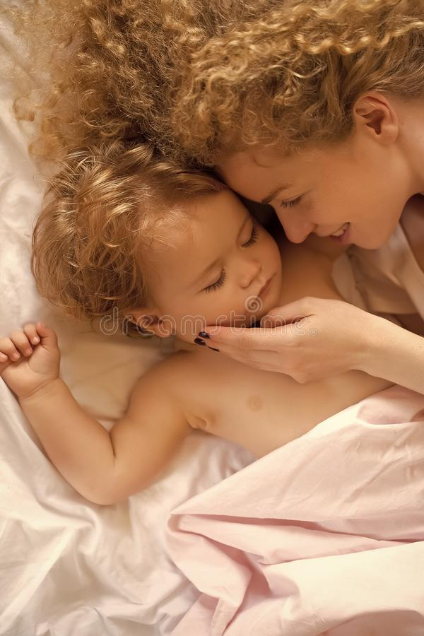 Mother with baby sleeping. Closeup of young beautiful loving mother with light blonde curly hair touching small tiny cute male lovely baby sleeping indoor in bed royalty free stock photos