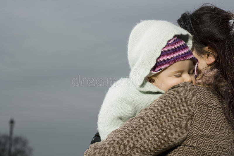 Mother With Baby Sleeping In Her Arms. Closeup of young mother with baby sleeping in her arms stock photography