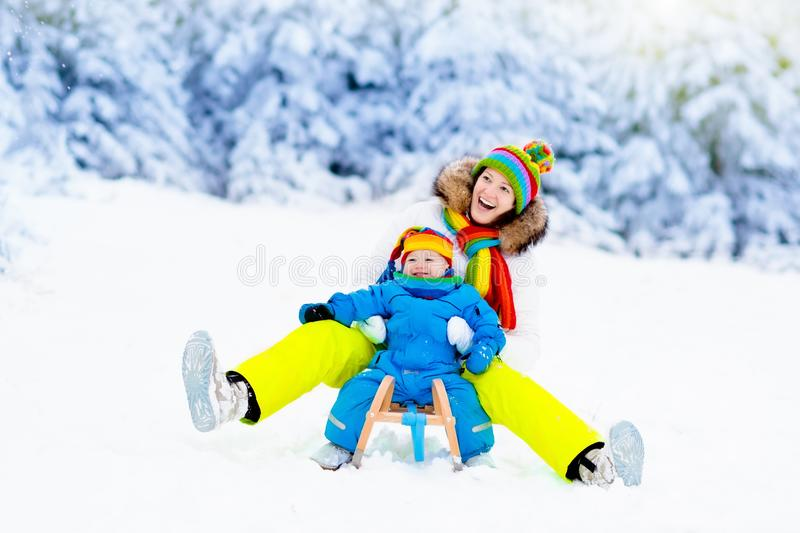 Mother and baby on sleigh ride. Winter snow fun. Mother and baby on sleigh ride. Child and mom sledding. Toddler kid riding sledge. Children play outdoors in stock photography