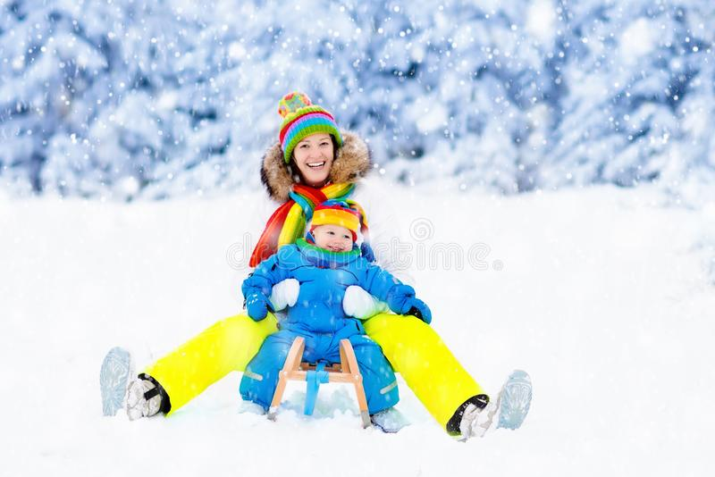Mother and baby on sleigh ride. Winter snow fun. Mother and baby on sleigh ride. Child and mom sledding. Toddler kid riding sledge. Children play outdoors in royalty free stock photography