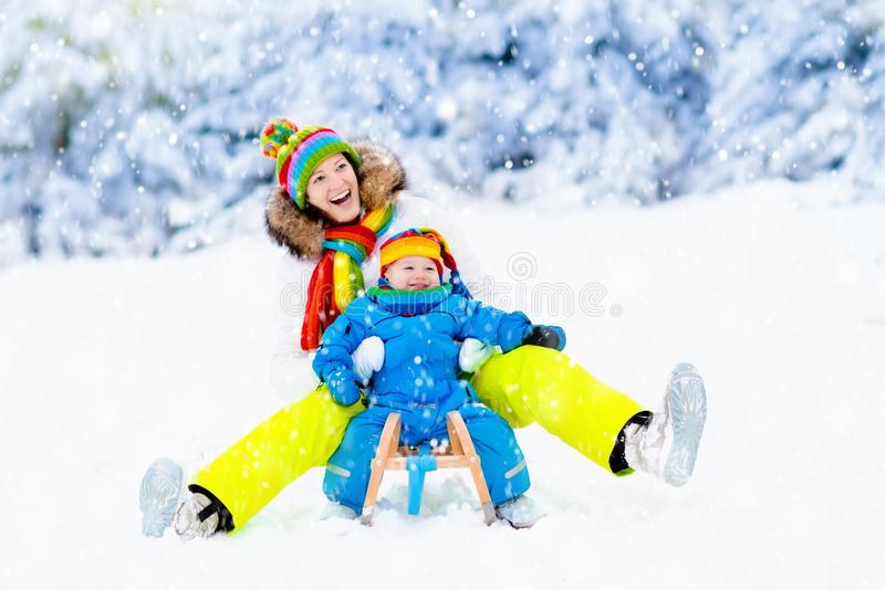 Mother and baby on sleigh ride. Winter snow fun. Mother and baby on sleigh ride. Child and mom sledding. Toddler kid riding sledge. Children play outdoors in stock images