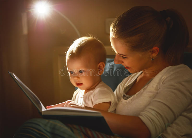 Mother and baby son reading a book in bed. Before going to sleep stock images