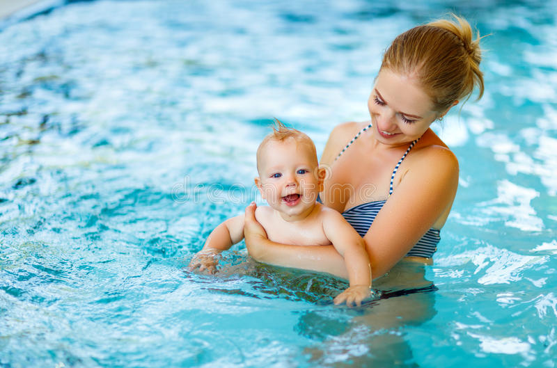 Mother and baby swim in pool stock photos