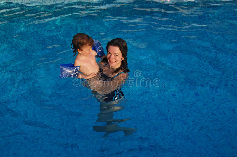 Mother and baby in swimming pool. Mother and her child having fun in swimming pool stock photography