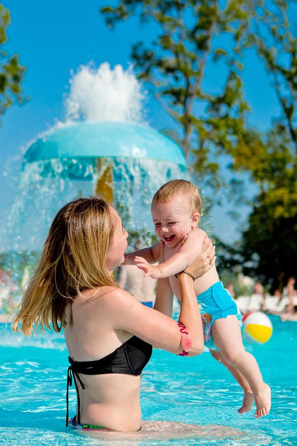 Mother and baby in swimming pool. Parent and child swim in a tropical resort. Summer outdoor activity for family with kids. royalty free stock images