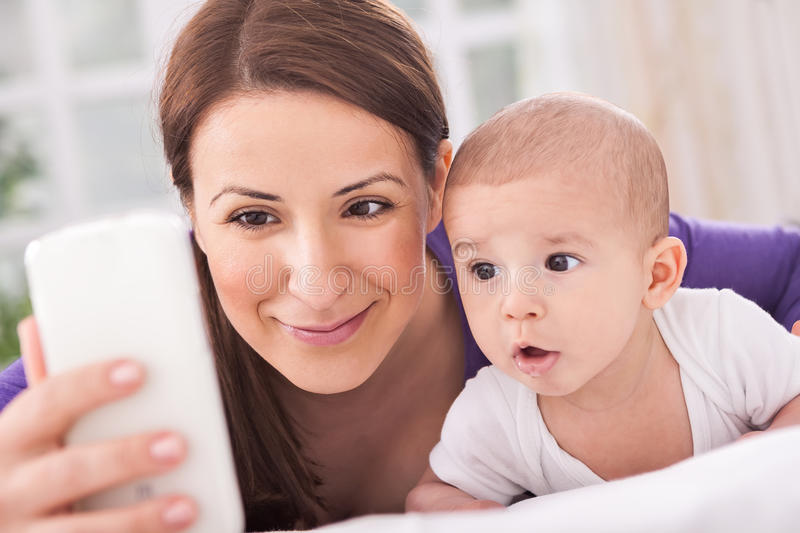 Mother and baby talking with father on phone stock photography