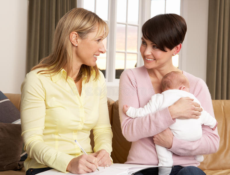 Mother With Baby Talking With Health Visitor stock images