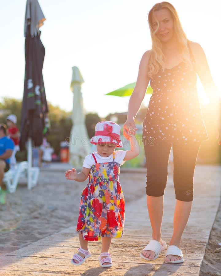 Mother with baby toddler girl during sunset on the beach. Summer stock images