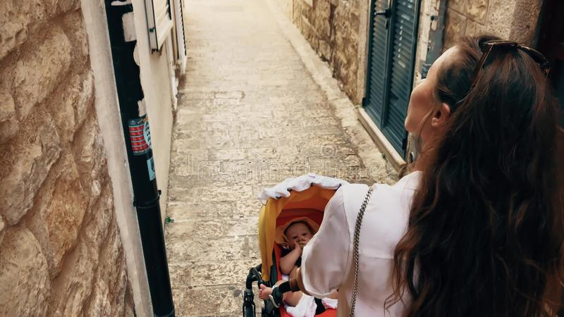 Mother and baby walk in Montenegro old town with a stroller. Mom and her baby traveling in old town with a stroller stock photo