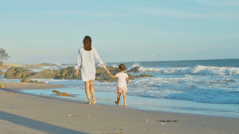 Mother with baby walking on sea coast with holding hands. stock image