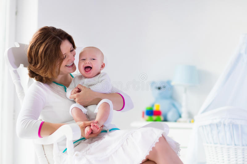 Mother and baby in white bedroom. Young mother holding her newborn child. Mom nursing baby. Woman and new born boy in white bedroom with rocking chair and blue royalty free stock image