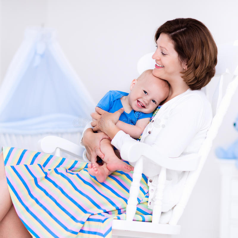 Mother and baby in white bedroom. Young mother holding her newborn child. Mom nursing baby. Woman and new born boy in white bedroom with rocking chair and blue stock photos
