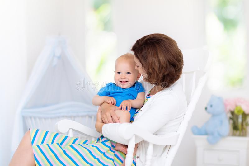 Mother and baby in white bedroom royalty free stock photography