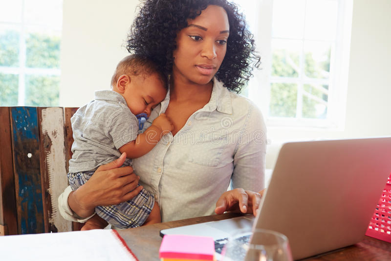 Mother With Baby Working In Office At Home stock photo