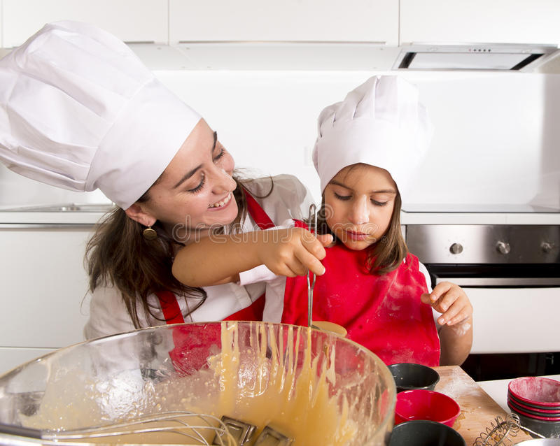 Mother baking with little daughter in apron and cook hat filling mold muffins with chocolate dough royalty free stock photos