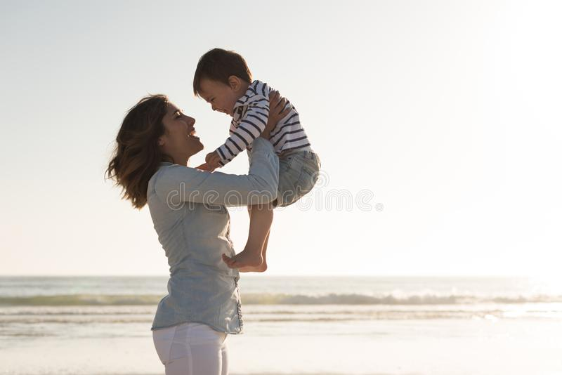 Mother at the beach with her baby. Young mother exploring the beach with her baby stock photography