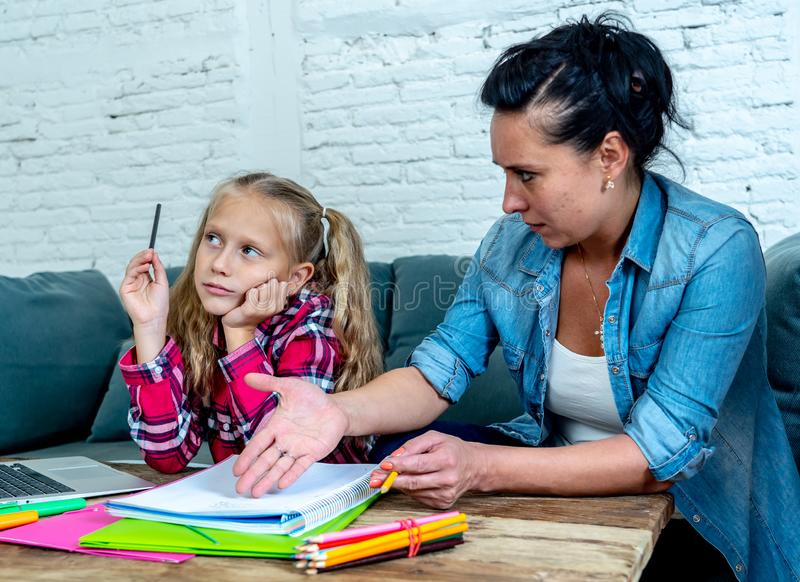 Mother becoming frustrated with daughter whilst doing homework sitting on sofa At home in learning difficulties homework parenting royalty free stock photography