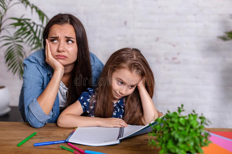 Mother becoming frustrated with daughter whilst doing homework sitting at the table at home in learning difficulties. Homework. Parenting and education concept royalty free stock image