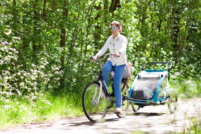 Mother on bicycle with baby bike trailer in park. Young mother riding bicycle with baby bike trailer in sunny summer park. Fit active woman cycling with child royalty free stock photography