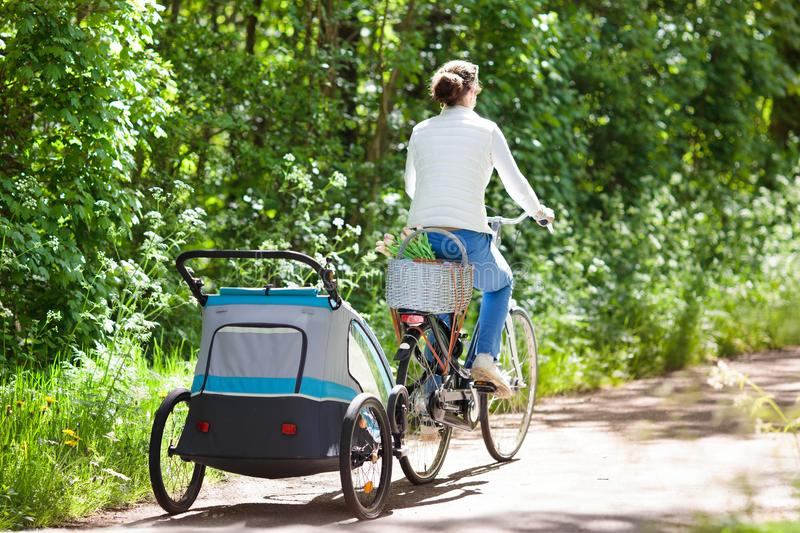 Mother on bicycle with baby bike trailer in park stock image
