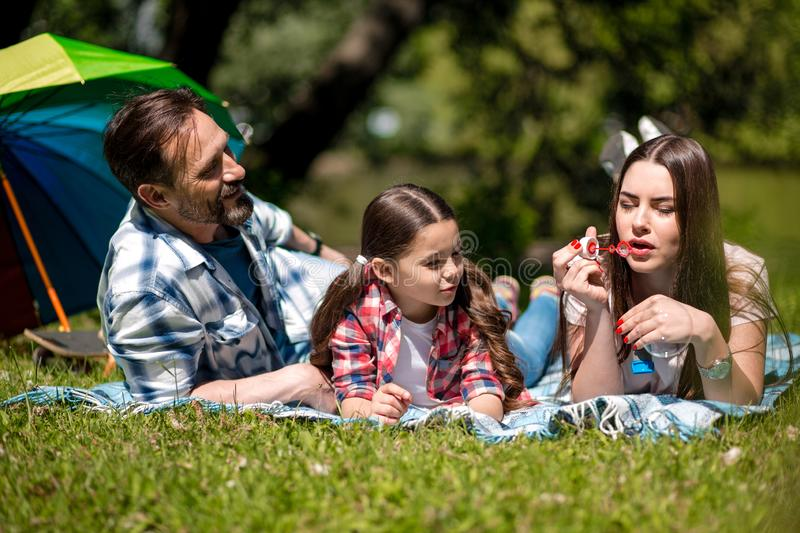 Mother Is Blowing Bubbles While Lying On The Blanket In The Park With Husband And Daughter.Colorful Umbrella Is On The royalty free stock photo