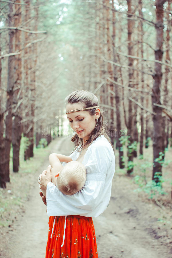 Mother breast-feeding a baby in nature royalty free stock photo