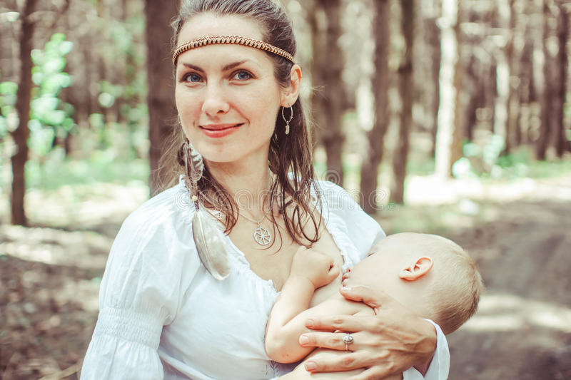 Mother breast-feeding a baby in nature royalty free stock photography