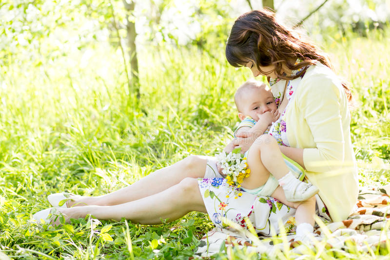 Mother breast feeding baby outdoors royalty free stock photography