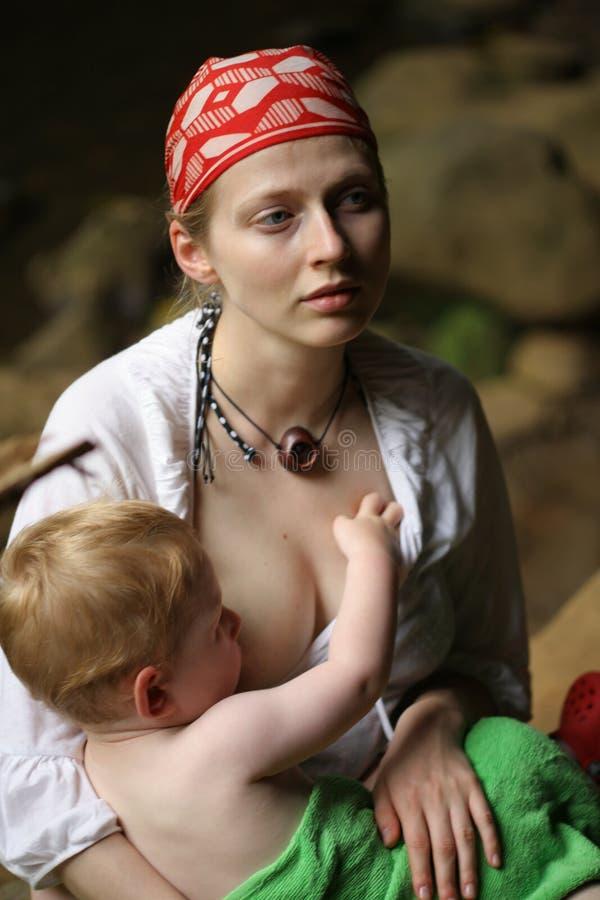Mother breastfeeding child. Mother breastfeeding small child outdoors stock photos
