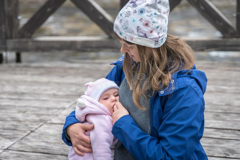 Mother breastfeeding her newborn baby girl in the park royalty free stock images