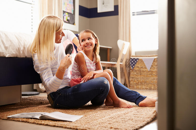 Mother brushing young daughter's hair royalty free stock photography
