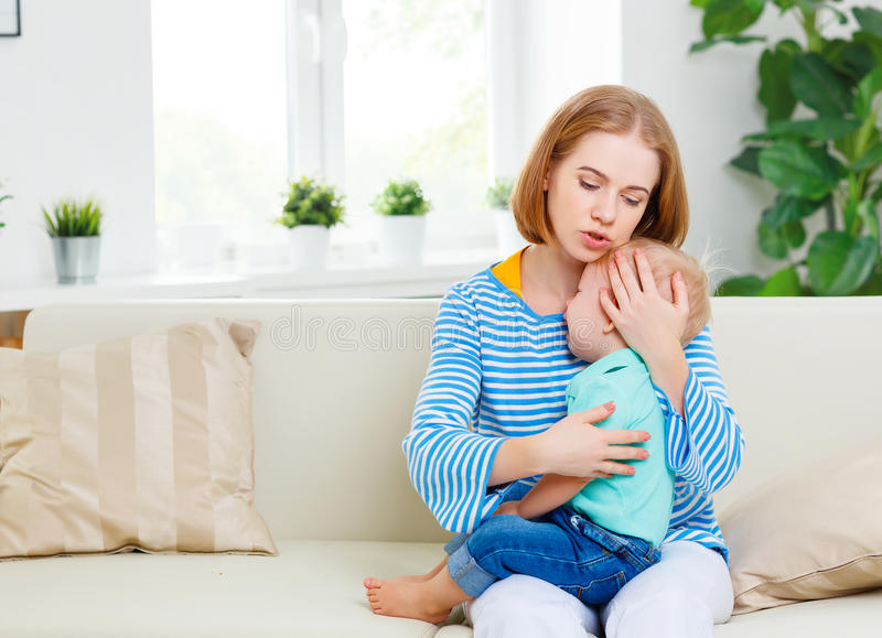 Mother calms crying baby son. Mother calms crying child baby son royalty free stock photography