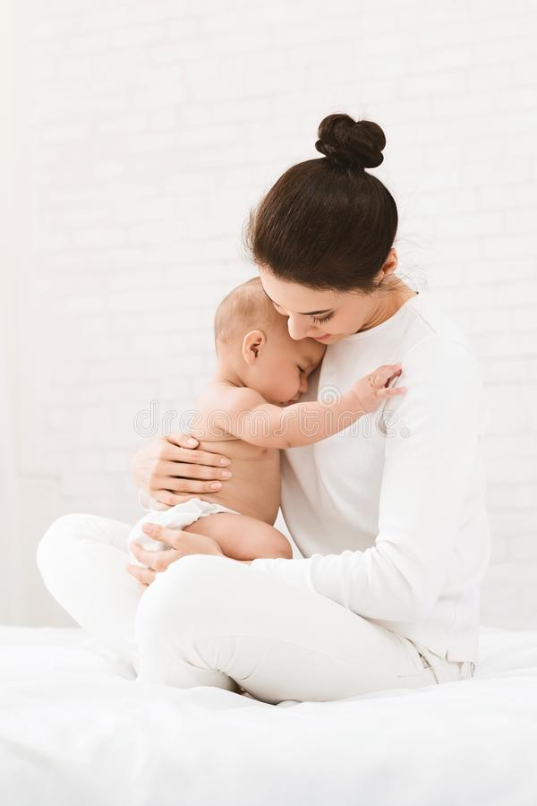 Young mother holding her newborn child in hands stock image