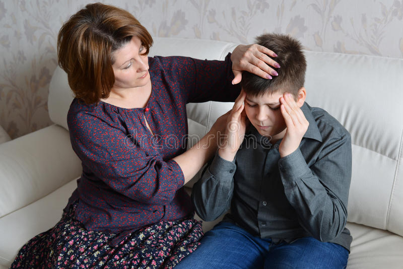 Mother cares for her son who has headache stock images