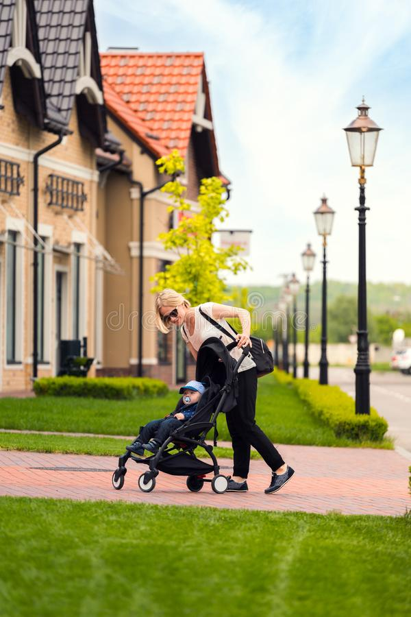 Mother carries her child in a stroller for a walk. Happy mother looks into the stroller to check her baby, happy family, walk with the child in the fresh air stock photos