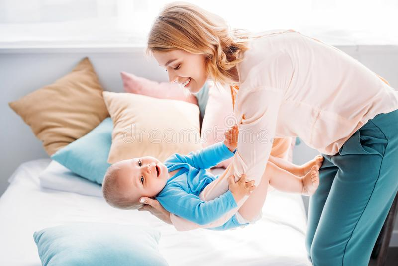Mother carrying adorable little child over bed. At home stock photos