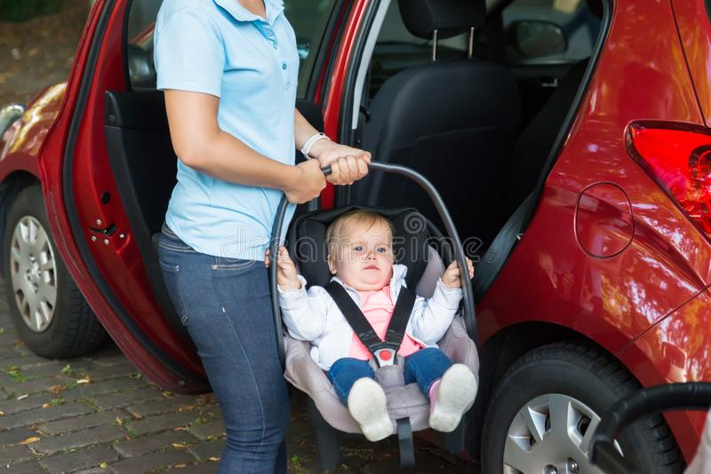 Mother Carrying Baby On Car Seat stock photos
