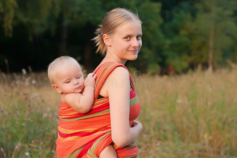 Mother carrying daughter in sling royalty free stock photos