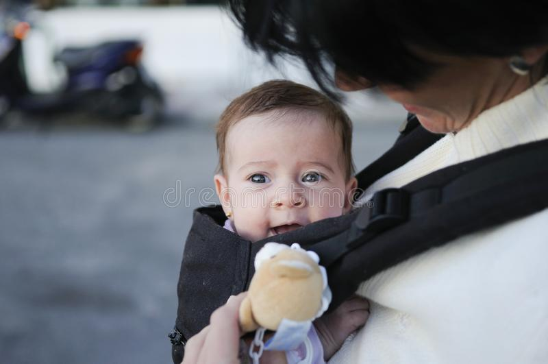 Mother carrying her baby girl in a baby carrier royalty free stock images