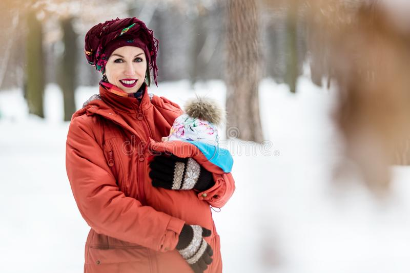 Mother carrying her baby girl wears red jacket and sling stock photography