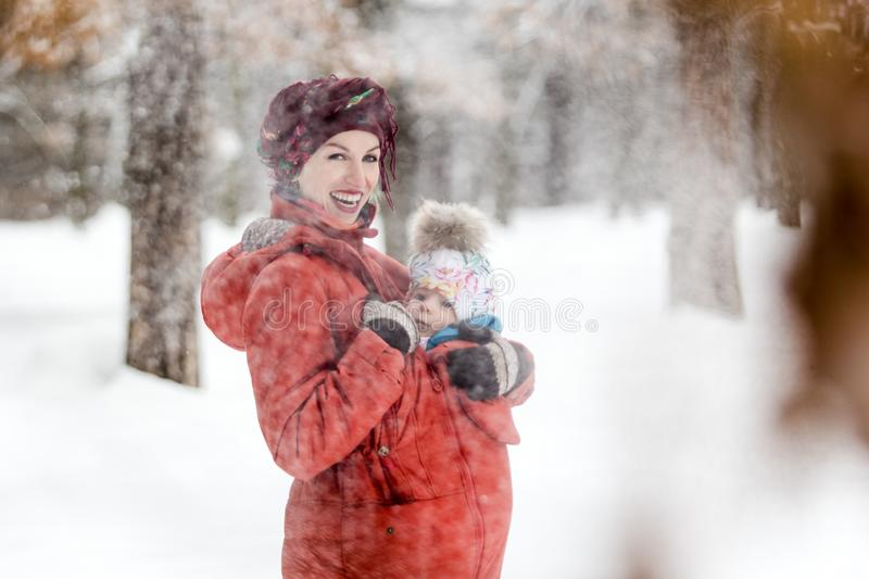 Mother carrying her baby girl wears red jacket and sling stock photo