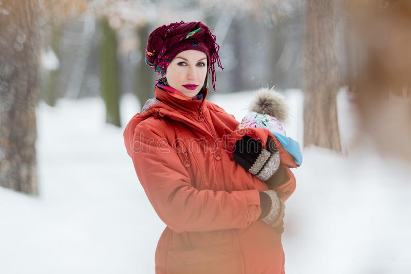 Mother carrying her baby girl wears red jacket and sling royalty free stock image