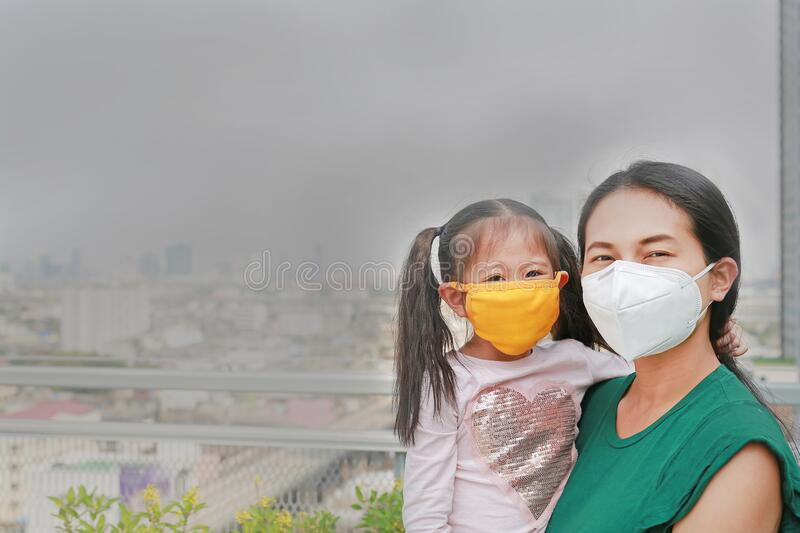 Mother carrying her daughter with wearing a protection mask against PM 2.5 air pollution in Bangkok city. Thailand royalty free stock photos